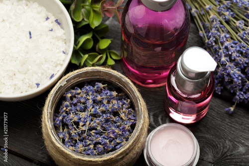 Aromatic composition of lavender, herbs, cosmetics and salt on a dark table top - 211779177