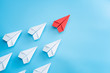 Leadership concept with red paper plane leading among white on blue background