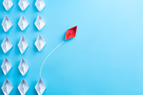 Group of white paper ship in one direction and one red paper ship pointing in different way on blue background. Business for innovative solution concept. - 211787350