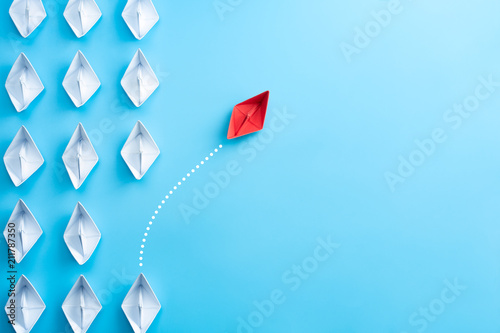 Leinwanddruck Bild Group of white paper ship in one direction and one red paper ship pointing in different way on blue background. Business for innovative solution concept.