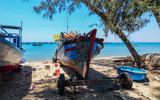 Maintain fishing boats on beach - 211790336