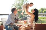 Lovely family sitting on a terrace, having breakfast - 211790751