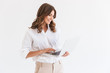 Leinwanddruck Bild - Portrait of adorable smiling woman with long brown hair holding and looking at silver laptop, isolated over white background in studio