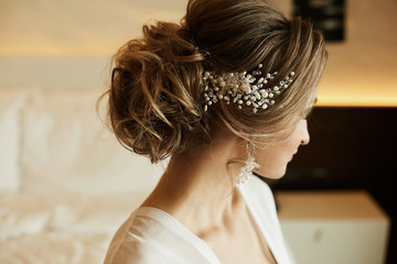 Wedding hairstyle of beautiful and fashionable brown-haired model girl in a lace dress, with earrings and jewelry in her hair © innarevyako