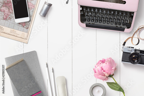 styled feminine desk background with various writing supplies, vintage camera and pink peony - top view, copyspace for your text - 211803317