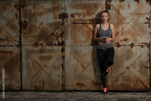Aluminium Fitness Beautiful young sporty woman listen music and relax near rusty industrial door in urban environment