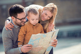 Happy family with  map are ready to travel.