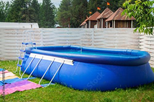 Blue inflatable pool among garden - 211811373
