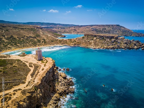 Ghajn Tuffieha, Malta - Beautiful Ghajn Tuffieha Bay, Ghajn Tuffieha Watch Tower and Riviera beach from above on a bright summer day with Gnejna Bay and blue sky at background