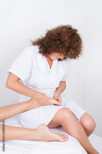 foot massage by curly woman therapist