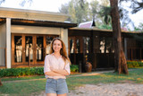 Young woman standing near resort house, wearing jeans shorts and blouse. Concept of summer vacations and female person. - 211821734