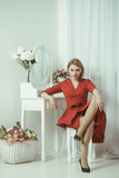 Woman in red dress. sexy woman grooming in morning at mirror. bedroom decor for elegant woman. confident and beautiful. Be A Woman A Man Needs. - 211822738