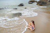 Little girl with doll wearing swimsuit and sitting on sand in sea waves in morning. Concept of summer vacations and childhood. - 211822917