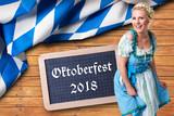 junge Frau im Dirndl vor Hintergrund mit bayrischem Rautenmuster und Aufschrift