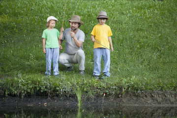 Happy boy and father go fishing on the river, children with a fishing rod on the shore of the lake