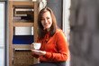 Female office assistant smiling while having cup of coffee. Happy young beautiful businesswoman holding coffee cup and looking at camera with genuine smile on her face.