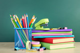 School supplies with books and notebooks on chalkboard background