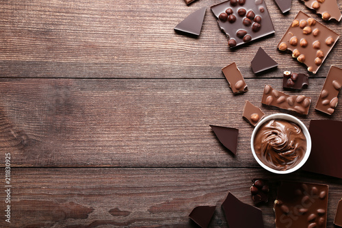 Chocolate pieces with nuts and bowl on wooden table - 211830925