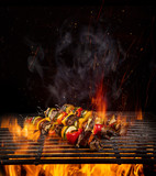 Chicken skewers on the grill with flames