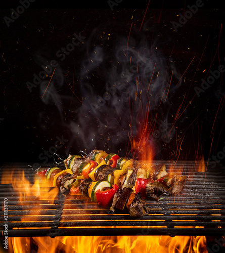 Leinwanddruck Bild Chicken skewers on the grill with flames