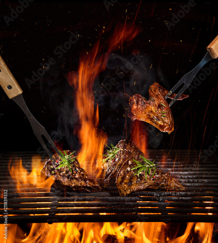 Beef steaks on the grill with flames - 211839332