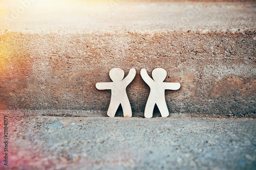 Wooden little men holding hands on natural stone background. Symbol of friendship, love and teamwork