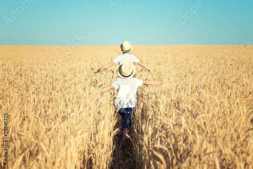 Leinwanddruck Bild Two brothers run around the wheat field.