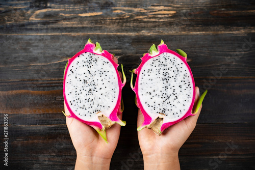 Foto Murales Half dragon fruit holding by hand on wooden background, top view, tropical fruit