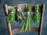 Bunches of herbs hanging on old wooden chair. Thyme, sage, rosemary, oregano. - 211878961