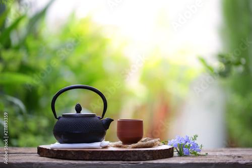 Stary czarny herbaciany garnek z brown filiżanką i kwiatem