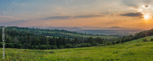 Fotobehang Zalm Sunset in the evening sky against the backdrop of green hills and massive vast mountains