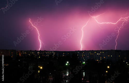 Fotobehang Aubergine Lightning strikes down over the city at night. Beautiful shot. Long Exposure Photography