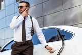 Handsome security guard listening message with security earpiece on street and opening car - 211900364