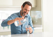 Leinwanddruck Bild - Middle age man drinking a glass of water with a happy face standing and smiling with a confident smile showing teeth