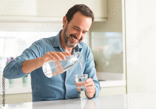 Leinwanddruck Bild Middle age man drinking a glass of water with a happy face standing and smiling with a confident smile showing teeth