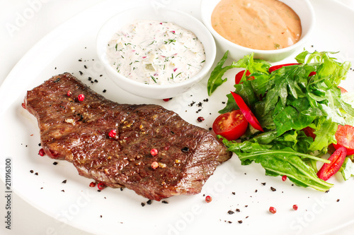 Fotobehang Steakhouse Meat steak beef with fresh vegetables, herbs and two kinds of sauces on white dish