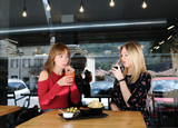 pretty young women drinking in cafe - 211917966