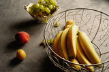 Fresh and juicy fruits, bananas, peaches, grapes on a gray background. Healthy diet