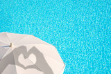 Shadows of hands forming a heart on a white parasol, blue swimming pool water background, summer concept - 211924148