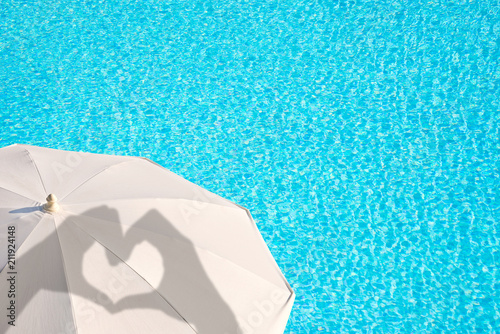 Leinwanddruck Bild Shadows of hands forming a heart on a white parasol, blue swimming pool water background, summer concept