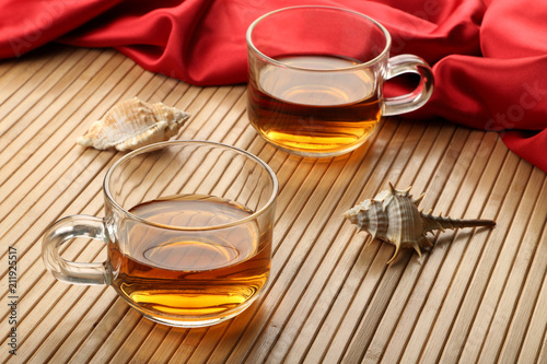 Fototapeta Two Cups of Tea on Wooden Table Mat with Sea Shells