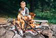Leinwanddruck Bild - Boy sits near campfire. Summer camping time