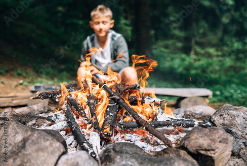 Leinwanddruck Bild Boy sits near campfire. Summer camping time
