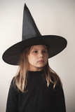 Girl in black witch costume over white wall - 211930107