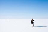 Teenage girl in black walks on frozen Sea - 211930132