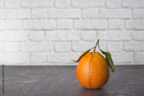 pojedyncza sicilian pomarańcze z liśćmi na ciemnym tle i białym ściana z cegieł