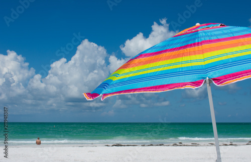Tropical beach with colorful umbrella, blue sky, clouds, woman sitting alone. - 211948387