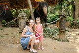 Young woman with little daughter standing near tamed and tied elephants. Concept of traveling with children to exotic countries and wild domesticated animals.