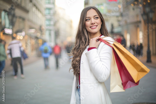 fototapeta na ścianę Beautiful woman walking in the street, holding shopping bags