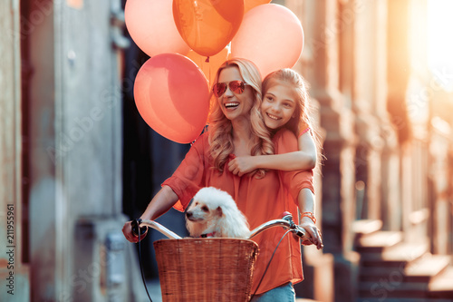 Beautiful mother and daughter having fun in city